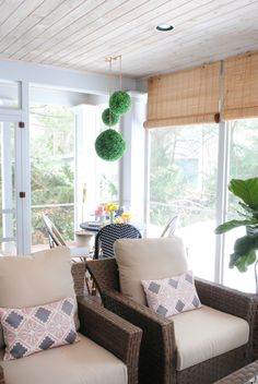 A small woven wicker dining set on a screened in porch