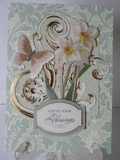 This is a larger 5 x 7 card with embossed card layer, gold foil flourishes, layered, die cut Daffodils, butterfly and dimensional label stamped