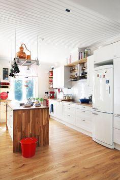 Valkoiset keittiökalusteet ja kannellinen metallitynnyri on ostettu Ikeasta. Tyyliä täydentävät punaiset KitchenAidin keittiö-koneet ja Coca-Cola-tarjotin.