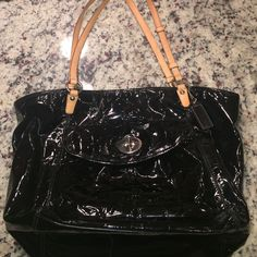 Coach black patent leather purse with embossed 'C' Coach purse. Black patent leather and tan straps. Blue inside. Zipper closure. Embossed Coach symbol all over outside. Excellent condition. No signs of wear. No stains. No trades. Coach Bags Shoulder Bags