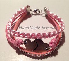 Braccialetto realizzato a mano con tre tipi di fili rosa : cordino coda di topo a treccia, cordino cerato con distanziatore con 2 cuori, e filo al alcantara piatto con strass.
