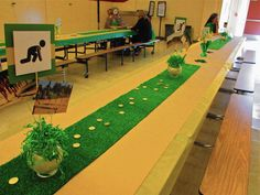 Track and Field Banquet Colored tablecloths were placed on tables, brown craft paper was then layered on top and finally faux grass carpet was cut be become a table runner.