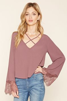 A woven blouse featuring a V-neckline, a strappy front, long bell sleeves with eyelash lace cuffs, and a flowy silhouette.