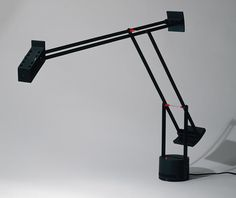 """With the """"Tizio"""" lamp, designer Richard Sapper sought to redesign the standard desk lamp. Using a sensitive counterweight system, the adjustable arm of the lamp can be manipulated into almost any position, allowing the user to direct the light source exactly where it is needed most. The arms themselves conduct electricity to the bulb, eliminating the need for extraneous wires and facilitating the precise balance of the arm"""