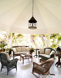 "This covered porch has a mix of antique wicker; the fabric is ""lemonade- and sangria-proof,"" says designer Robin Bell. Because who wants to clean up a mess after a relaxing afternoon?"