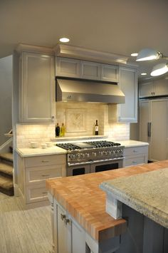 grey cabinets w/ off white subway tile- love the butcher block wood also... not a fan of stairs right behind...