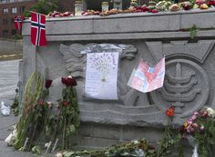 """""""Grief in the public domain"""". Flowers, flags, lights and greetings laid outside Oslo City Hall."""