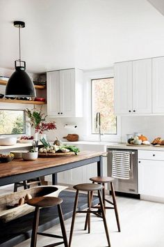 Modern, classic, industrial and farmhouse country-infused styles perfectly blended together in this bright kitchen filled with traditional recessed panel white upper and lower kitchen cabinets with black hardware, open wood shelving, chrome and brushed satin finish appliances, domed black pendant lights, backless wood bar stools, and an unfinished wood farmhouse dining table as a kitchen island.