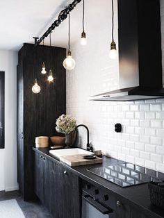 Edison light bulbs against clean white subway tiles and deep black furniture.