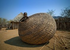 Girl from the Mundimba tribe inside a gigantic basket, Angola. These giant baskets are used to store the beans in the Mundimba tribe of southern Angola. The girl is inside to get a goat that jumped inside to sleep. Photo by Eric Lafforgue Eric Lafforgue, Willow Weaving, Basket Weaving, Woven Baskets, Wicker Baskets, Tribal People, Textiles, African Art, African Culture