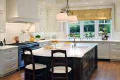 White kitchen with white drum pendant lights over dark kitchen island with marble countertops