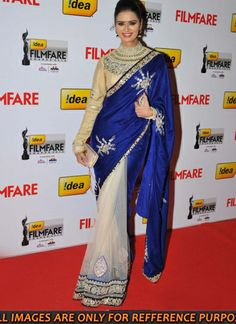 Bollywood South Indian actress meenakshi dixit looked stunning in blue and white colour Net Party wear saree. This designer bollywood replica saree is build of white net fabric and blue velvet fabric with attractive border . Blouse of this designer saree is build of dupion. Petticoat is build of Satin fabric. Buy bollywood style party wear latest designer saree for your next big event and function from Indian Trendz.