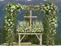Styled by  Bluebird Productions , gorgeous greenery drapes this altar at an  outdoor wedding .