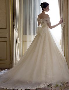 Off the shoulder lace, satin and tulle A-line wedding dress. Notice the detailing of the back — those buttons and that bow! This gown is just too gorgeous. It's incredibly affordable, too! Get it in standard sizing or made with your exact measurements.