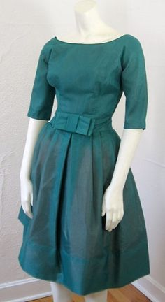 Fantastic organza dress from late 1950's, made of sheer iridescent organza, three quarter length sleeves, scooped neckline, and a very full pleated skirt with a big bow at the waist front. Features a wide flattering waistband and a tulle crinoline underskirt to add fullness.