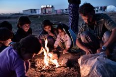 Syrian Kurdish refugees try to get warm around a fire at a refugee camp in the town of Suruc, Sanliurfa province, on November 7, 2014.