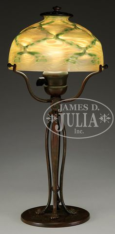 """. Tiffany Studios desk lamp has cats paw adjustable base with three arm spider. Base is finished in rich brown patina with green and red highlights. Signed on the underside """"Tiffany Studios New York 427″. Base supports a favrile glass shade with raised diamond pattern which is highlighted with green iridescence all against a gold iridescent King Tut design. Shade is signed in the fitter """"L.C.T."""" Lamp is finished with an original acid etched Tiffany heat cap"""