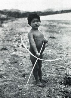 """Niño alacalufe con arco y flecha. Fotografía de Martín Gusinde. 1920 aprox. En: """"Los indios de Tierra del Fuego: los Halakwulup"""""""". Martín Gusinde. Editorial C.A.E.A .1986."""