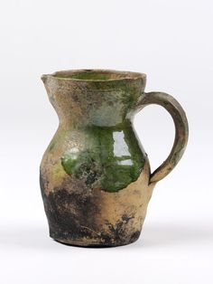 Jug of lead-glazed earthenware. Pear-shaped body, short neck and broad cup-shaped top with small lip spout. Facetted loop handle. Burn marks on base.  Place of Origin  England, Great Britain (made) Hampshire, England (possibly, made)  Date  ca. 1550-1650 (made)