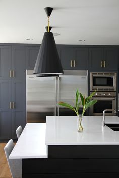 Kitchen Reveal. Blue grey cabinets, quartz countertops, a dash of open shelving, subway tiles and a pair of Jonathan Adler Antwerp pendants.