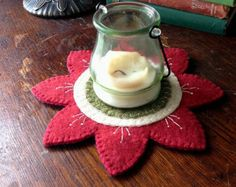 This rustic, Americana style candle mat measures 8 inches in diameter. The background is a lovely plaid in muted burgundy, blue and cream. It has cream stars appliqued around the perimeter with reclaimed and antique white buttons in the center of each one. A cream blanket stitch travels around the perimeter. -All my items are hand stitched and made from reclaimed materials. The wool felt that I use is from wool garments and blankets that I felt. Some of the buttons that I use are vintage…