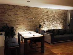 Wohnzimmer mit Essbereich mit dunklen Möbeln und Steinwand aus Riemchen als Wandverkleidung
