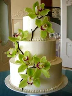 Round three tier wedding cake covered in royal icing and decorated with green Cymbidium Orchids. From www.edithmeyer.com