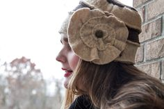Sometimes the day calls for subtle and classic colors. This fabulous cloche hat is understated but never boring. This Impossibly Cute Hat is fashioned of fine wool culled from cast-off sweaters and is designed to flatter your darling face. The flirty flower is anchored with a vintage brass-tone button and draws the attention to your soulful eyes. Everyone will want to look as classy and fabulous as you! Our hats are always lined in fleece for comfort and extra warmth. In shades of camel and…