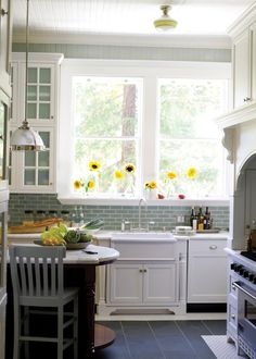 White cabinetry with matching subway tile and paint in a blue-green-grey.