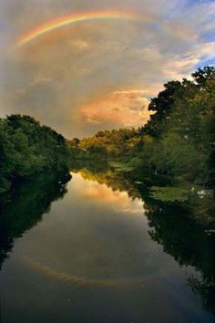 After a summer shower in Medford the Mystic River was aglow aided by the illumination of a rainbow.  Photography by Stan Grossfeld