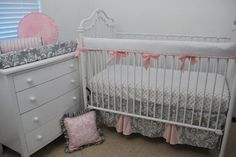 White crib rail guard with pink trim and bows to coordinate with the Grey Damask and pink skirt pleats and throw pillows