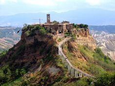 Civita de Bagnoregio perches on top a tall point surrounded by cliffs.  There is only one small bridge large enough for a golf cart to transport goods to town.