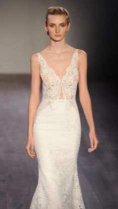Ivory venise lace trumpet bridal gown, V neckline front and back, shear appliqued bodice, cut out side panels on skirt, chapel train. Available in Ivory.