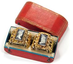 Bracelets | English (likely) | c.1830 (possibly earlier) | The Three Graces (georgianjewelry.com) ----- The matched pair is made of four parts each, a rectangular top, two sides & a hinge with back flap. A long pin secures each bracelet. Each miniature portrait is under glass.    Zeus & Hera reigned supreme among the Greek gods & goddesses in classical mythology. Rendered en grisaille, gray & black upon ivory on an inky black background, the miniature portrait pair faces each other for all…
