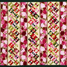 A scrappy assortment of green, red, and pink florals blooms across this wall hanging. Wide sashing and Four-Patches show off both large and small prints.