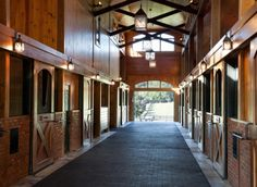 Love the combination of wood, brick, iron and beams in this horse barn. It's nice that the stall doors have openings for the horses to stick their heads out.