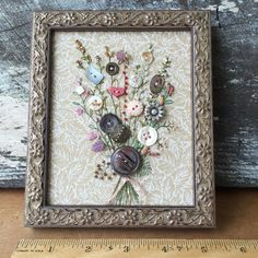 Handsewn framed picture using Antique Buttons as flowers with embroidered stems and leaves then embelished with beads as buds. Stretched on acid-free foamcore and framed in wood. The back is covered with old paper a sawtooth hanger and 2 rubber bumpers. Measuring 6.5high x 5.5wide and .5deep.