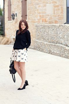 Printed dress worn as a skirt, slouchy black sweater, black wedges with sparkle detail and simple gold jewelry.