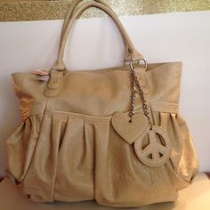 Sale...Gorgeous leather like bone colored purse . Brand new leather like bone colored purse with heart and peace sigh dangles. Soft. Good size purse with 3 pockets on the inside and 1 on the outside. Perfect for summer. Bags