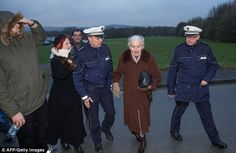 Holocaust denier Ursula Haverbeck (second right) is taken away by the police after she tried to attend the trial