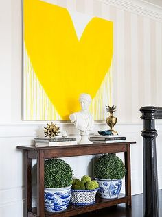 At the landing at the top of the stairs, a picture of a giant heart provides a clever contrast to the otherwise traditional decor. | Inside Sue De Chiara's Gorgeous Connecticut Home That's Full-On Fun
