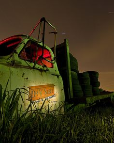 Forgotten flatbed truck, disappearing into the weeds beside the train tracks, in a vacant lot, in the industrial part of Stockton, California.    Night, combination of 1 and 8-minute exposures. Full moon, overcast, mercury and sodium vapor light, natural and red-gelled flashlight.