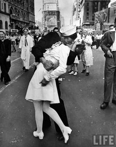 Alfred Eisenstaedt: A jubilant American sailor clutching a white-uniformed nurse in a back-bending, passionate kiss as he vents his joy while thousands jam Times Square to celebrate the long awaited-victory over Japan, New York, 1945.