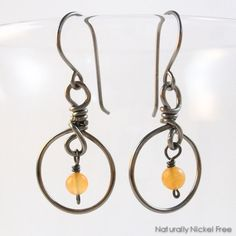 Niobium dangle earrings with a small peach aventurine bead dangling within a wire frame. The bead is just 4 mm in size, these allergy safe earrings are 1.5 inches long. Bright color, fun movement. Niobium is dark metallic gray in color, it will no...