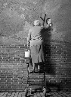Old lady spray painting graffiti on a brick wall..