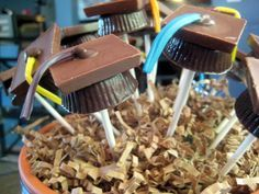 You can use a peanut butter cup as the base, or a portion of a cake ball.  Use Hershey's Cacao Reserve Milk Chocolates as the tops, and Rainbow Twizzlers as the tassels.