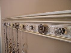 Trim board painted with decorative cabinet knobs for hooks