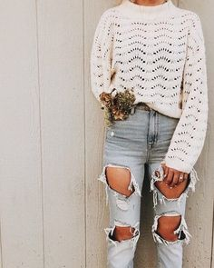 Cute winter white sweater with trendy distressed denim jeans.