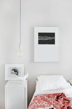 Dormitorio de un piso madrileño de 50 metros cuadrados. La fotografía sobre mesilla es de Man Ray y la de la pared de Renato D´Agostin (ambas en 'Mondo Galería'). Cola de ballena de 'The Interiorlist'. Lámparas Base de 'NUD Collection'. AD España, © Asier Rua