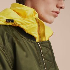 A Burberry bomber jacket with a contrast detachable warmer. The laid-back shape is detailed with multiple zip pockets and finished with contrast knit trims